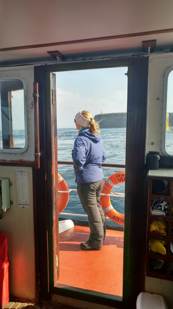 Tara Callahan - one of last year's sea watch foundation interns is attending orca watch this year and helping with ferry data collection. Duncansby head visible behind her. Photo credit: Chloe Robinson/ Sea Watch Foudation.